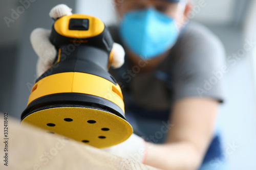 Fotografia, Obraz Male handy man hold yellow grinder with disc sander in hand closeup background