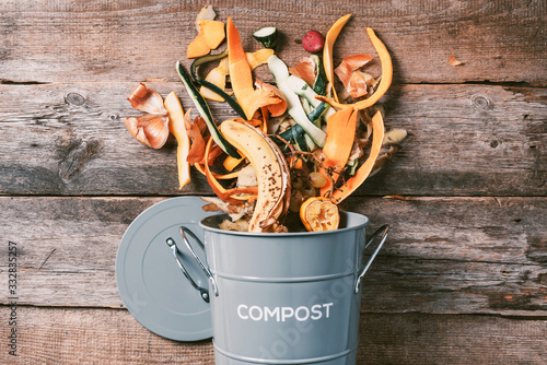 Peeled vegetables on chopping board, white compost bin on wooden background. Top view of kitchen food waste collected in recycling compost pot.