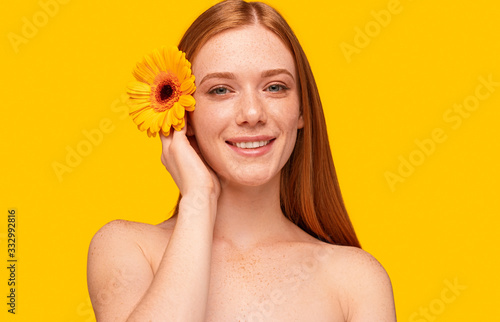 Young ginger model with flower smiling at camera Fototapeta