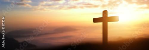 Leinwand Poster Silhouette of catholic cross at sunset background