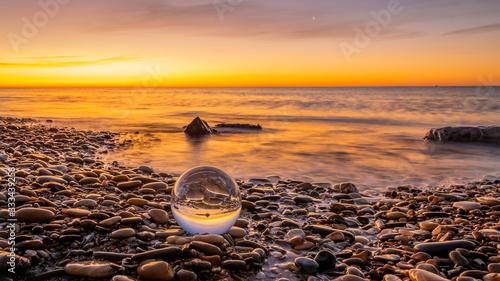 Leinwand Poster Boule de cristal sur des galets d'une plage au lever de soleil.