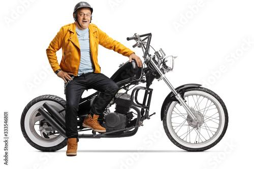 Fotografiet Mature biker smiling and sitting on a chopper motorbike