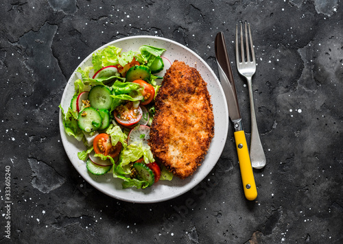 Obraz na plátně Chicken milanese and fresh romaine salad, cherry tomatoes, radishes, cucumbers s