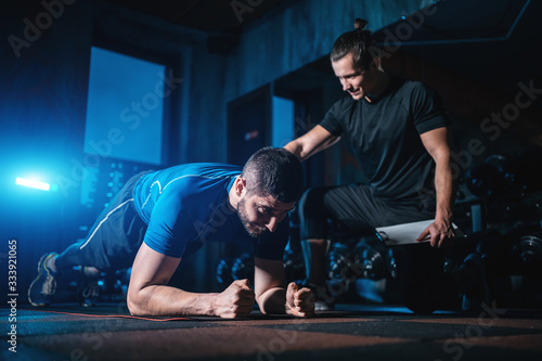 Leinwand Poster young man has workout with personal trainer in modern gym