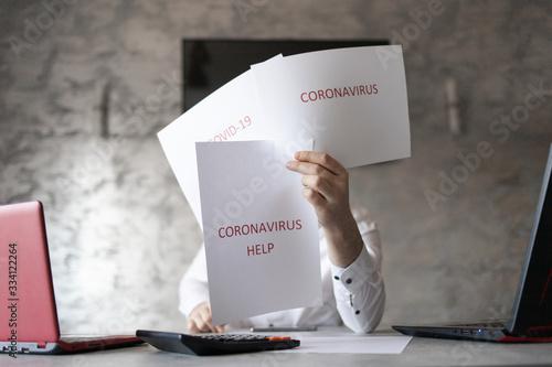 Pracownik w biurze trzymający kartki z napisami coronavirus, covid przed sobą. Biurko z laptopem, dokumetami i kalkulatorem. Coronavirus HELP
