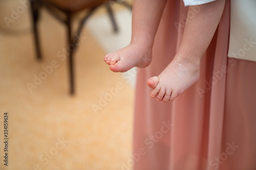 Tablou Canvas feet baby in arms of godfather in baptism.