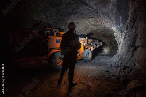 Stampa su Tela Man miner in underground quartz mine tunnel with scoop machine