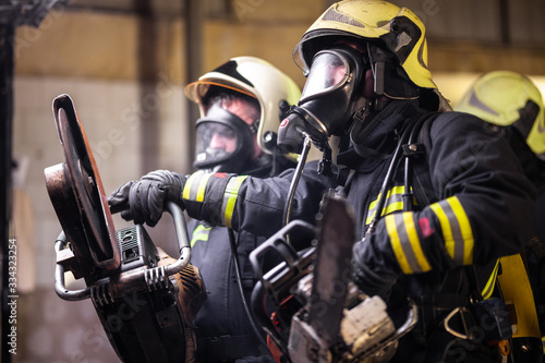 Group of professional firefighters wearing full equipment, oxygen masks, and emergency rescue tools, circular hydraulic and gas saw, axe, and sledge hammer Fototapeta