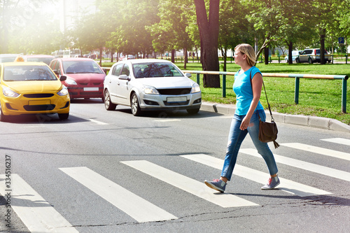Slika na platnu Woman crossing street at crosswalk