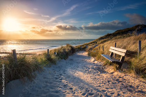 evening sunshine over bench and path to sea beach Fototapet
