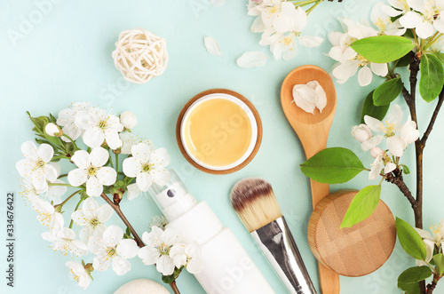 Beauty spa treatment, honey facial mask, skincare cosmetic products with natural spring apple blossom top view over pastel colored blue delicate background