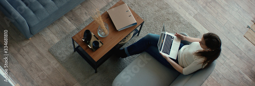 Fototapeta OVERHEAD Caucasian female working from home, having a video call with colleagues