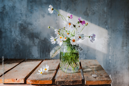 Fotografija Beautiful bouquets of wildflowers on a wooden table on a cold concrete wall background