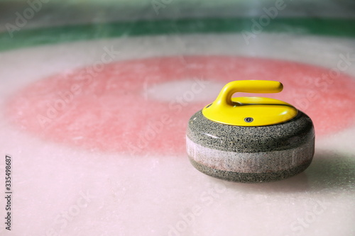 Cuadros en Lienzo curling stone is on ice near the home colorful background