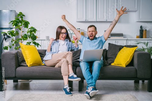 Fotografie, Obraz Young couple celebrating money win after betting online at bookmaker's website