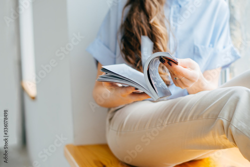 Photo home and leasure concept - smiling woman reading magazine at home near the windo
