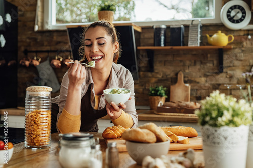 Smiling woman tasting food while cooking in the kitchen. Fototapeta