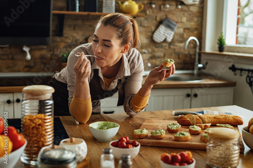 Foto Young woman eating while making avocado bruschetta in the kitchen