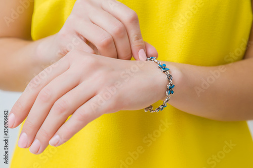 Stampa su Tela Young woman in yellow, bright clothes wearing blue flower bracelet on her hand wrist