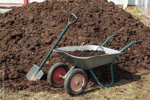 a heap of horse  manure with a wheelbarrow and a shovel Fototapeta