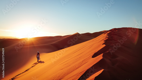 Stampa su Tela Silhouette Of Woman On Sand Dune In Desert Against Clear Sky