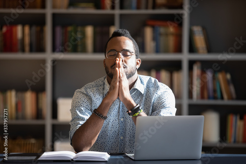 Fotografia Front view frustrated millennial african american guy sitting at able with computer, praying god with folded hands, asking good luck before business start