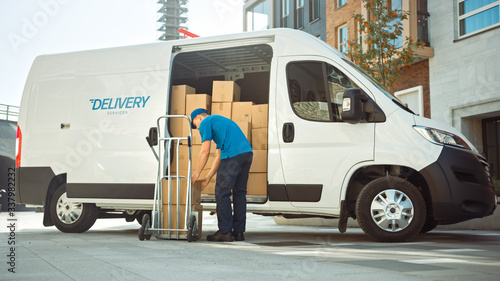 Fotografie, Obraz Courier Takes out Cardboard Box Package From Opened Delivery Van Side Door