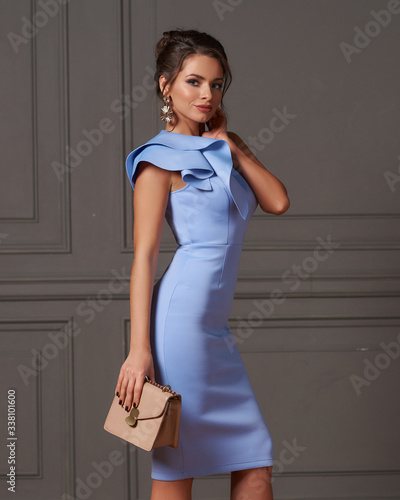 Beautiful slim pretty caucasian woman with hairstyle and makeup in blue evening Fototapet