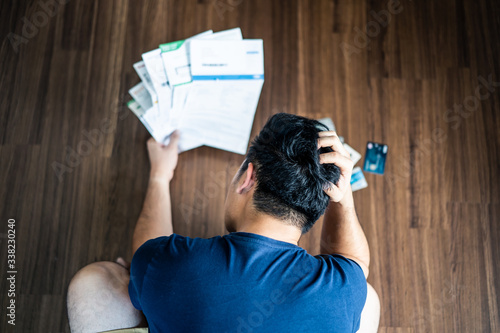 Fotografering Top view of stressed young Asian man hands holding the head trying to find money to pay credit card debt and all loan bills