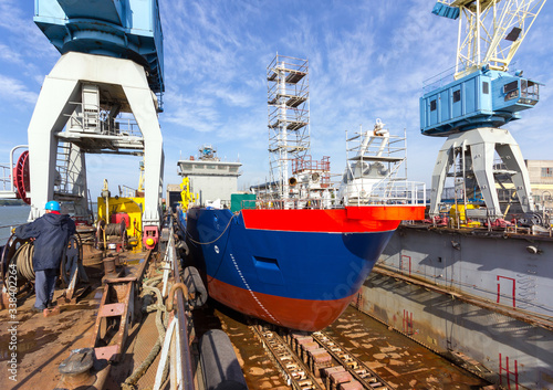Fotografie, Obraz A cargo ship is building in a dock at a shipyard