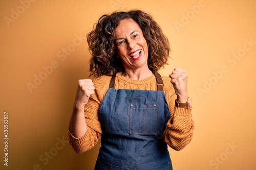 Canvas Print Middle age beautiful baker woman wearing apron standing over isolated yellow background celebrating surprised and amazed for success with arms raised and open eyes