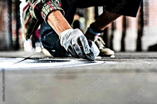 Fototapeta premium Cropped Image Of Hands With Glove Making Street Art