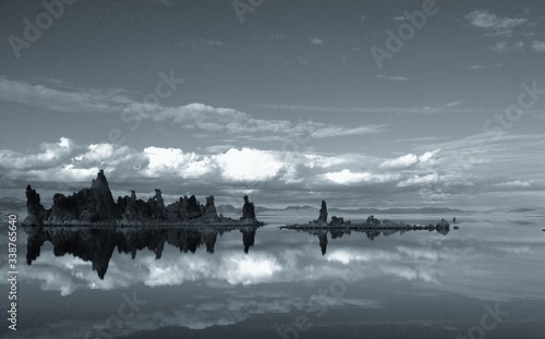 Obraz na płótnie Mid Distance Of Tufa Outcrops Reflected In Calm Lake Against Cloudy Sky