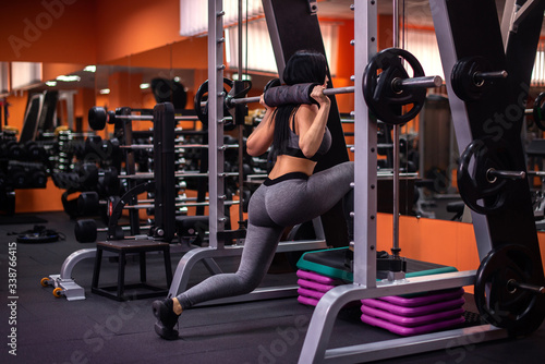 Leinwand Poster Fit woman doing lunges with the smith machine in gym