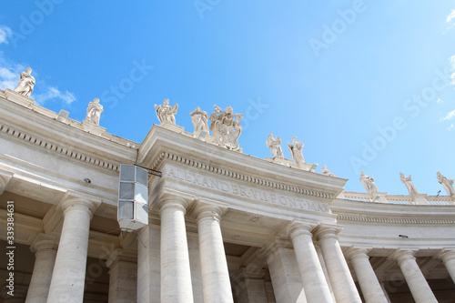 Fotomural Saint Statues on the colonnades of St Peter's Square with blue sky and clouds in
