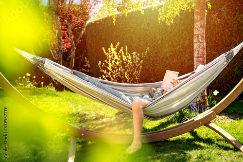 Photo Young relaxed girl reading book in hammock in garden at home at bright sunset