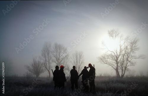 Fototapeta Hunters Standing On Grassy Field Against Sky During Sunrise In Foggy Weather