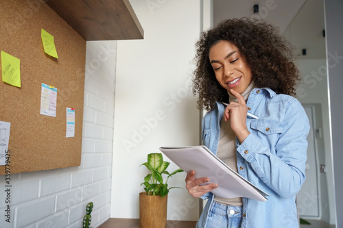 Wallpaper Mural Smiling african teen girl, afro american college student, ethnic school pupil, remote worker studying, distance learning holding notebook in hands, thinking, making notes working from home office