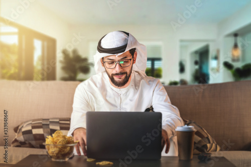 Tablou Canvas Arab man working from home sitting on sofa