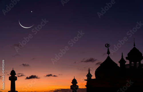 Obraz na płótnie Silhouette dome mosques on sunset sky background in the evening with crescent mo