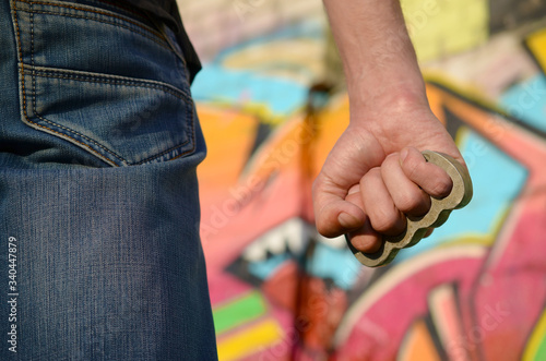 Fotografia, Obraz Back view of young caucasian man with brass cnuckle on his hand against ghetto brick wall with graffiti paintings