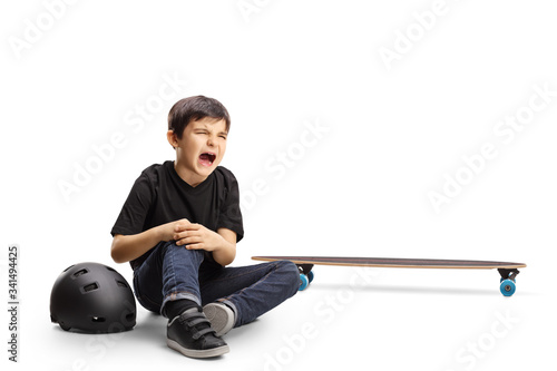Vászonkép Child sitting on the floor crying and holding knee hurt from a skateboard