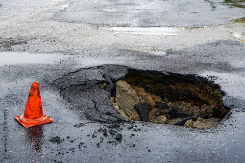 Fototapeta huge pit hole on the road, failure in the asphalt, marked with an orange cone, d