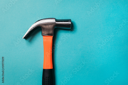 Fototapeta metal hammer with an orange handle on a blue background close