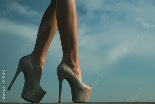 Fototapeta Close-up of young womans legs in high heeled shoes