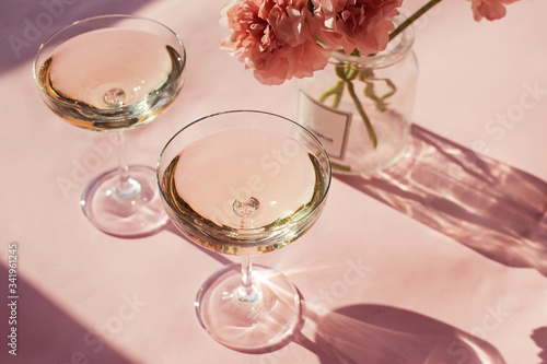 Two glasses of sparkling wine on a pink table