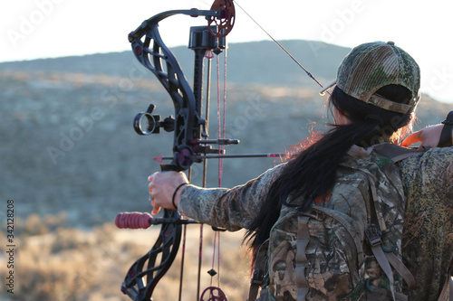 Female archery hunter drawing bow Fototapeta