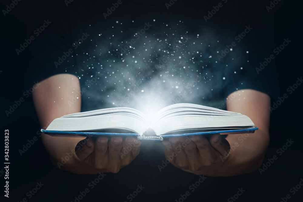 Man open magic book with growing lights and magic powder floating on the book, Learning, Education, Knowledge and religion concept.