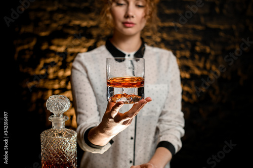 Valokuva Young beautiful bartender woman hold old-fashioned glass with alcoholic drink