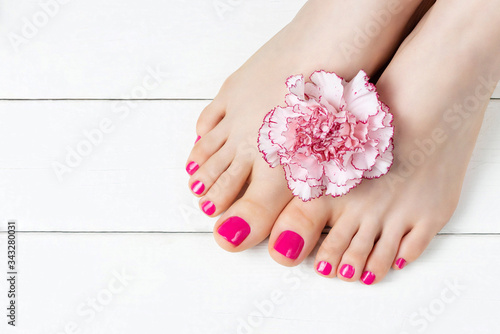 Pink pedicure with a flower on white wooden background, top view, copy space